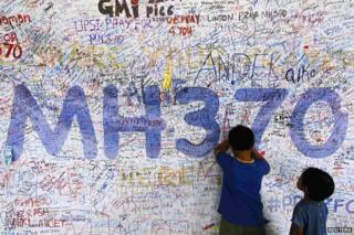 Children write messages on a wall at Kuala Lumpur Airport