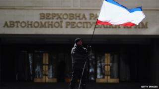 A man flies the Crimean flag outside the Crimean parliament in Simferopol