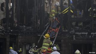 Rescue workers remove a body found in the charred remains of the Mariner's Cove Inn in New Jersey on 21 March 2014