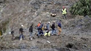Rescuers search the mudslide field on 26 March 2014