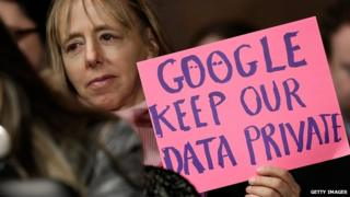 Woman displays a sign at a Senate hearing into Google activity