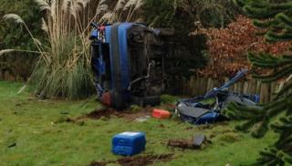 The car crashed through two gardens and ended up on its side
