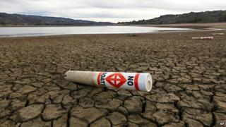 A warning buoy sits on the dry, cracked bed of Lake Mendocino, California