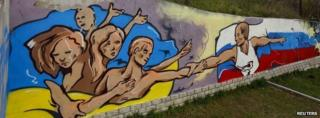 Graffiti depicting Russian President Vladimir Putin (R) extending a hand to the Ukrainian people is seen on a wall in the Crimean city of Simferopol on 28 March 2014.