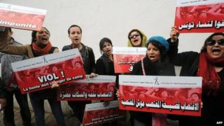 Tunisian activists hold placards during a demonstration against violence against women outside a court in Tunis hearing the trial of two Tunisian policemen accuse of raping a young woman. 31 March 2014