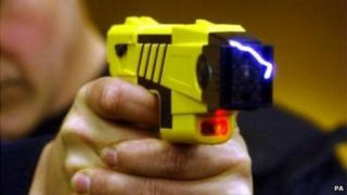 Taser being held by police officer