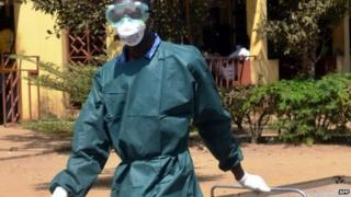A health worker in light protective gear walks on 31 March 2014 in the yard of the isolation ward of the Donka hospital in Conakry, Guinea