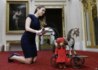 Curator poses with a doll and a horse on wheels.