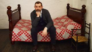 Ian Sansom sits on his bed with his head resting on his fist