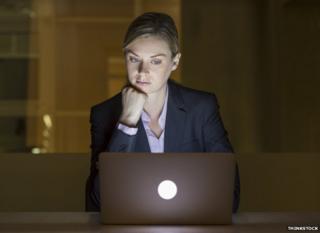 Woman looks at computer late at night