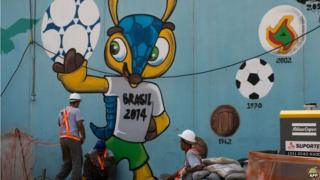 Workers rest next to a graffiti of Fuleco -the mascot of Brazil 2014 FIFA World Cup- near the Maracana metro in Rio de Janeiro on 8 April 2014.