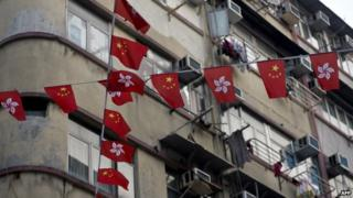Chinese and Hong Kong national flags hang before residential buildings in Hong Kong on 4 January 2014