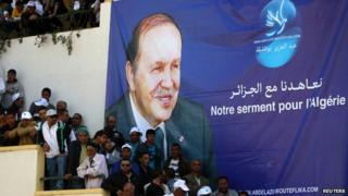 Supporters of Algerian President and presidential candidate Abdelaziz Bouteflika stand in front of his poster during a rally meeting in Annaba, east of Algiers