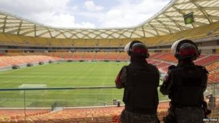 Riot police stand guard at the Arena Amazonia stadium in Manaus, on February 16, 2014.