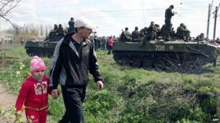 A father and his daughter walk past a column of Ukrainian armoured vehicles in Kramatorsk - 16 April 2014