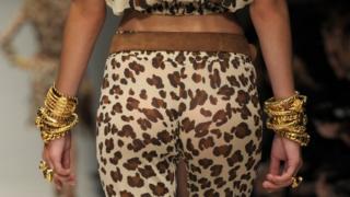 Female model's bottom in leopard skin trousers as she walks up the catwalk