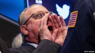 NYSE trader with Twitter logo behind him