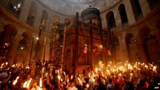 Christian pilgrims hold candles at the Church of the Holy Sepulchre in Jerusalem (19 April 2014)