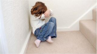 Young girl on stairs hiding her face
