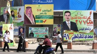 Iraqis walk past election campaign billboards in Kahramana Square, in the capital Baghdad, on 13 April 2014