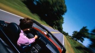 Man at wheel of fast car