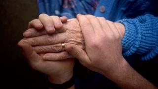 Carer holding the hand of an elderly woman