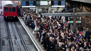 Commuters prepare to travel on the District Line of the London Underground which is running a limited service due to industrial action
