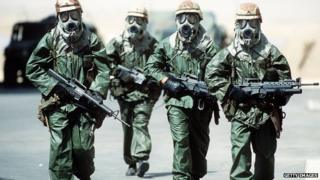 Soldiers walk around their camp wearing protective masks in this undated photo from during Operation Desert Shield