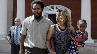 """Cornealious """"Mike"""" Anderson walks out of the Mississippi County Courthouse along with his wife, LaQonna Anderson, daughter Nevaeh, 3, and attorney Patrick Megaro, far left, after being released from custody, Monday, May 5, 2014"""