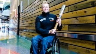 Josh Cassidy, in wheelchair, holds the Queen's Baton.