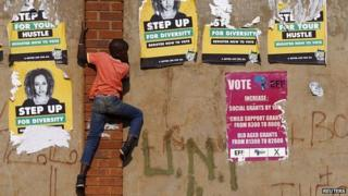 A child climbs past defaced election posters in Bekkersdal township, South Africa