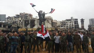 Government forces hang the national flag on top of a pole in the old city of Homs, Syria