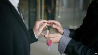 "A gay couple exchange rings during their ceremonial ""wedding"" as they try to raise awareness of the issue of homosexual marriage in central China's Hubei province (March 2011)"