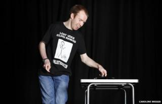 Lee Ridley onstage using his automated-speaking device