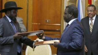 Ethiopian Prime Minister Hailemariam Desalegn, right, looks on as South Sudan's rebel leader Riek Machar, centre and South Sudan's President Salva Kiir exchange signed peace agreement documents in Addis Ababa, 9 May 2014