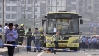 A paramilitary policeman runs in front of a bus after it was set on fire on a bridge in Yibin, Sichuan province, on 12 May 2014