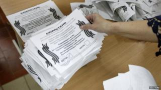 Member of local election commission sorts ballot after ballots were taken from ballot box as commission start counting votes of referendum on status of Luhansk