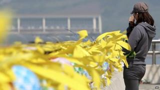 A volunteer wipes away tears near yellow ribbons with messages for the victims and missing passengers of the sunken ferry Sewol at a port in Jindo, south of Seoul, South Korea, 12 May 2014