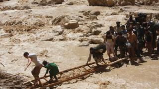Travellers use a ladder to cross a river where rains have washed away the main Mazar-Kabul highway