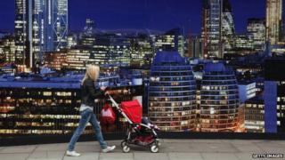 A woman walks by a luxury development advertisement in London