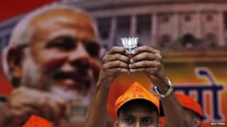 A supporter of Bharatiya Janata Party (BJP) holds a cut-out of lotus