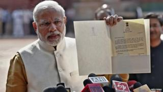 Narendra Modi shows a letter he received from President Pranab Mukherjee after meeting him at the Presidential Palace in Delhi May 20, 2014