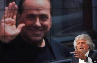 Beppe Grillo speaks on Italian TV with a portrait of Silvio Berlusconi on a giant screen behind him, 19 May