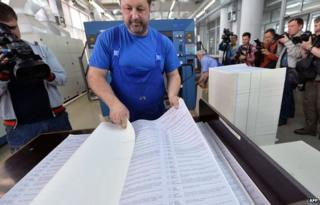 Photojournalists and cameramen film a worker examining ballots which will be use in early presidential election on May 25, during the printing process in printing house in Kiev on May 14, 2014.