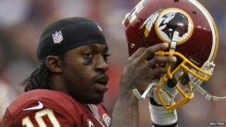 Washington Redskins quarterback Robert Griffin III puts his helmet back on after being tackled by the Baltimore Ravens defence in the first half of their NFL football game in Landover, Maryland 9 December 2012