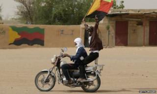 A Tuareg man waves the flag of the National Movement for the Liberation of Azawad (MNLA) in Kidal, northern Mali. File photo