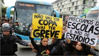 Striking teachers in front of Brazil football team's bus