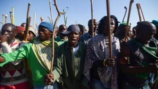Striking miners hold sticks as they dance and sing during a protest against their labour conditions, in the Wonderkop stadium in Marikana, South Africa, on 14 May 2014