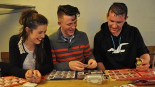 Abbie Dunnage, Josh Vartan and Adam Tucker swapping Panini World Cup 2014 stickers