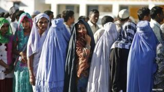 Muslim women, who were displaced by deadly religious strife last year, stand in a queue to cast their votes for the general election at a polling station in Palra village in Muzaffarnagar.